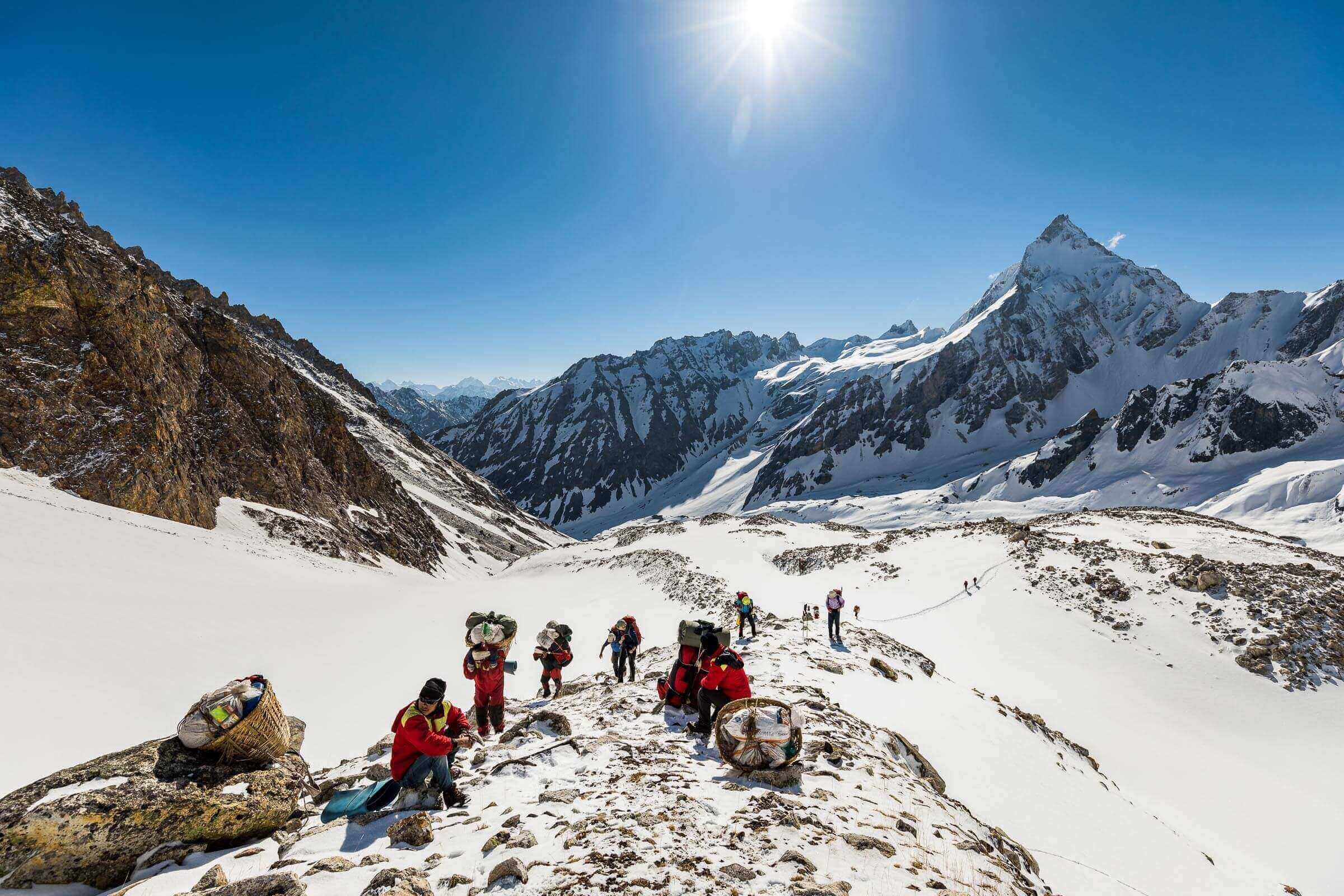 Trekkers and Nepali porters carrying loads up to a high pass in the north-west of Nepal