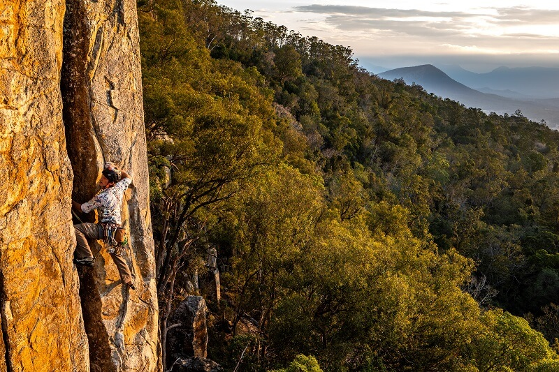 A rock climber, traversing the mountain with a beautiful backdrop, photographed using the Panasonic Lumix S5