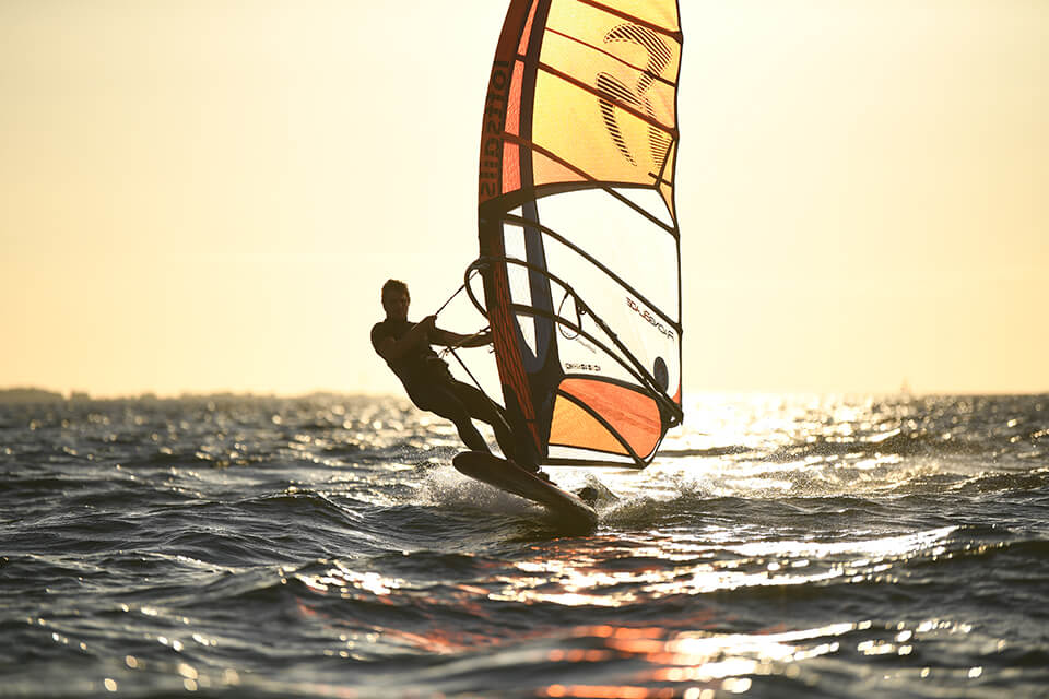 Windsurfer silhouetted against a bright golden sky, photographed with the