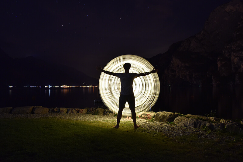 Silhouette of a man standing by the water with arms outstretched in front of a spiral of light, shot with the Nikon D5600