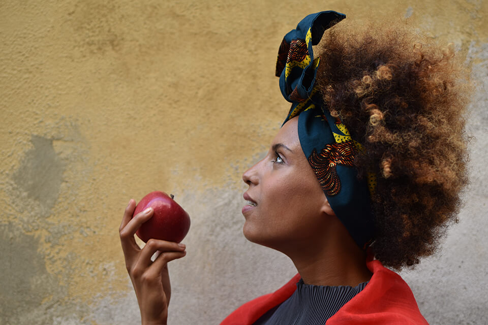 Woman with frizzy hair and blue headscarf looking up while holding an apple, photographed with the Nikon D5600 DSLR camera