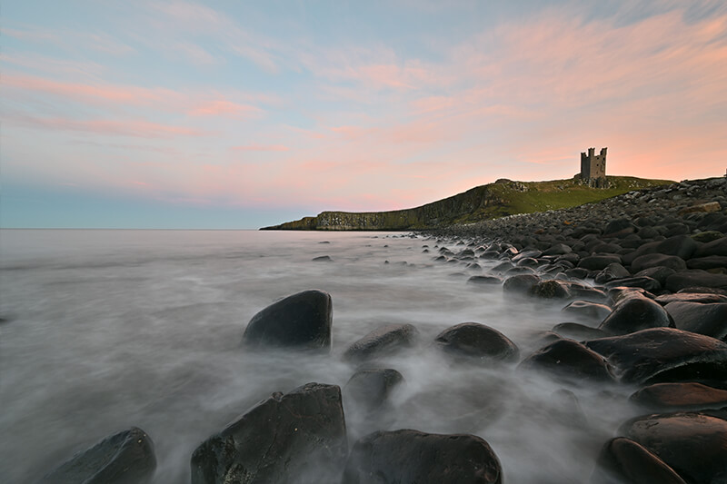 Ocean waves washing over rocks, with a castle atop a green hill in the distance, photographed with the Nikon Z 14-30mm lens