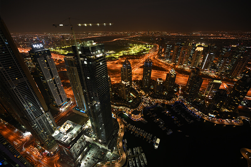 View over Dubai city buildings and waterfront at night, photographed with the Nikon Z 14-30mm lens