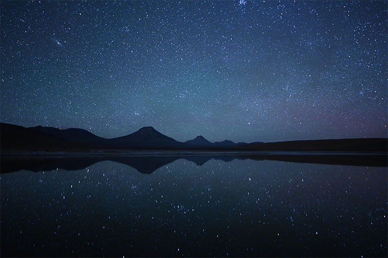 Mountains beneath starry sky reflected in water, shot in the Atacama Desert with the Nikon Z 20mm f/1.8 S lens