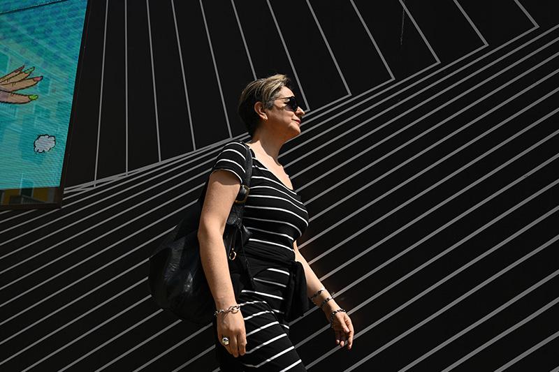 Woman in black and white striped dress walking past a black and white striped wall, shot with the Nikon Z 35mm f/1.8 S Lens