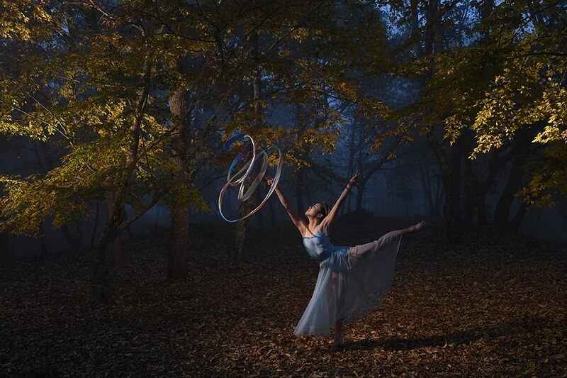 Ballerina on tiptoe, twirling a coloured ribbon amidst a misty forest, photographed using the Nikon SB-5000 flash