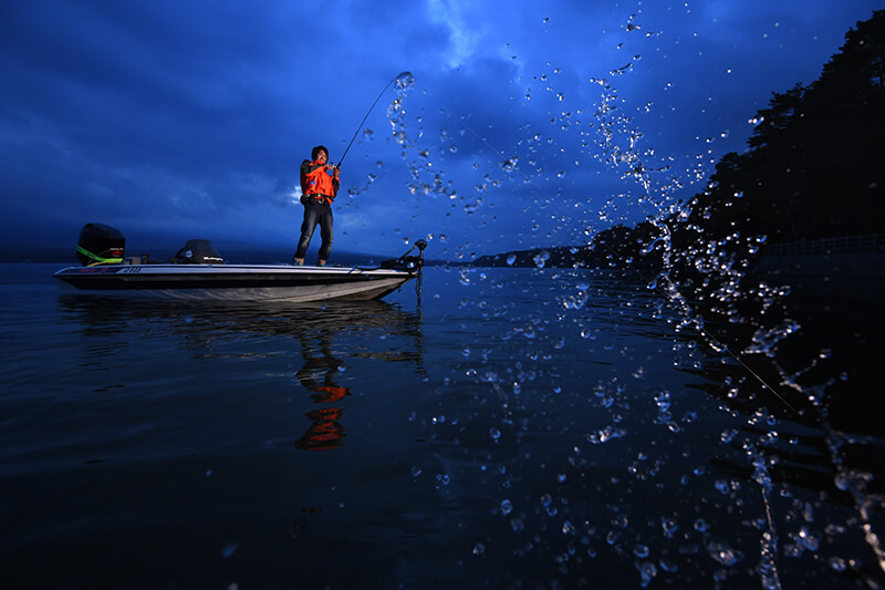 Fisherman standing in a dinghy while holding his fishing rod, with a splash of water in the foreground – photographed using the Nikon SB-5000 flash