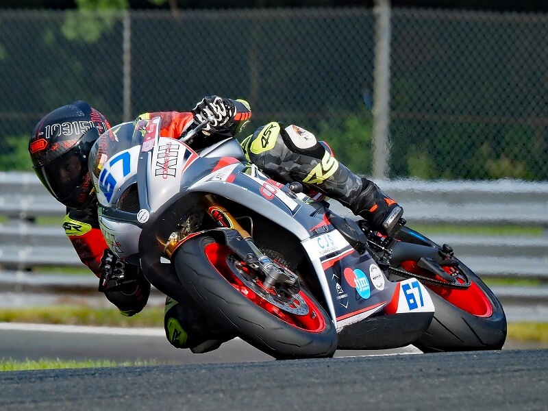 lose-up of motorcycle racer leaning into a track corner, photographed with the Olympus 150-400mm f4.5 TC1.25x IS PRO Lens