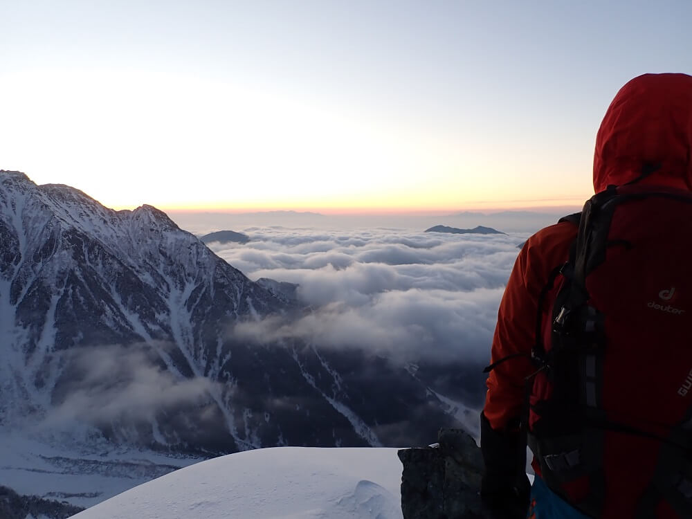 Hiker in red parka standing on a snowy mountain top looking towards the horizon, photographed with the Olympus TG-6
