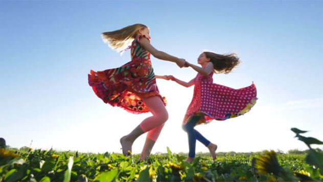 Two girls in cute dress dancing on the grass, photographed with the Panasonic LUMIX G7