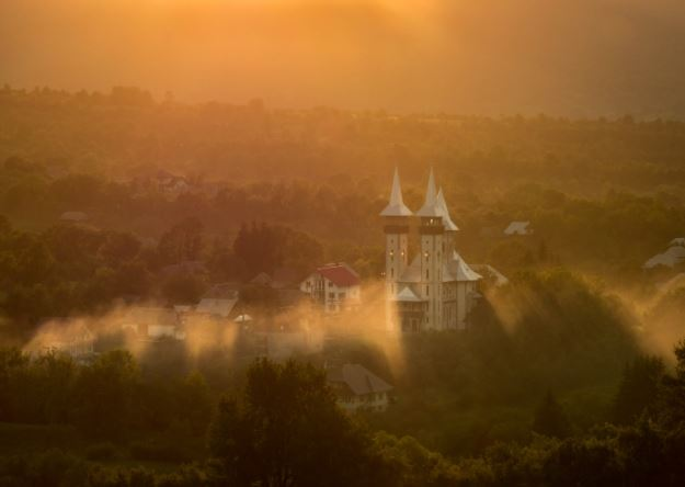 White church and surrounding buildings in a misty backlit landscape, shot with the Panasonic LUMIX VARIO 35-100mm f2.8 II Lens