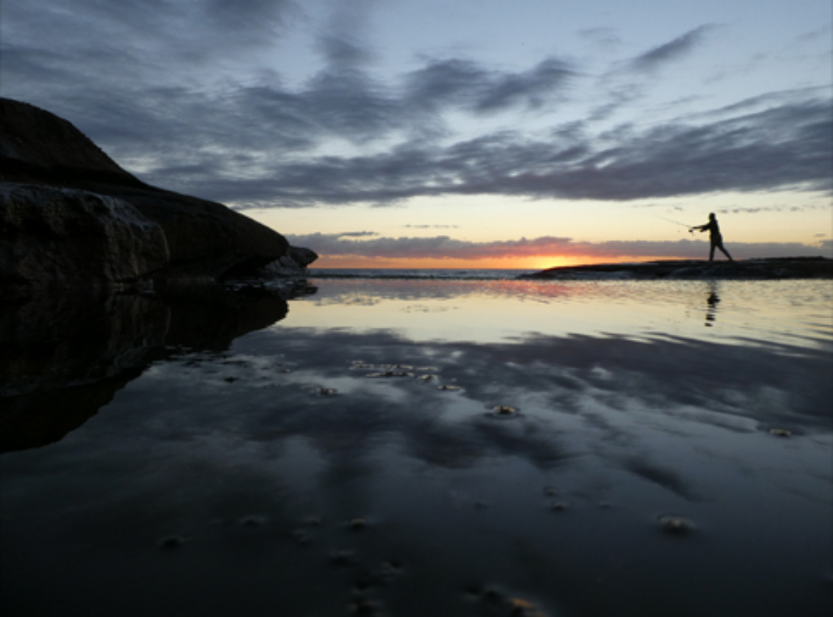 Fishermen casting a line into water reflecting the cloudy sunset sky, photographed with Panasonic Lumix TZ90 Compact Camera