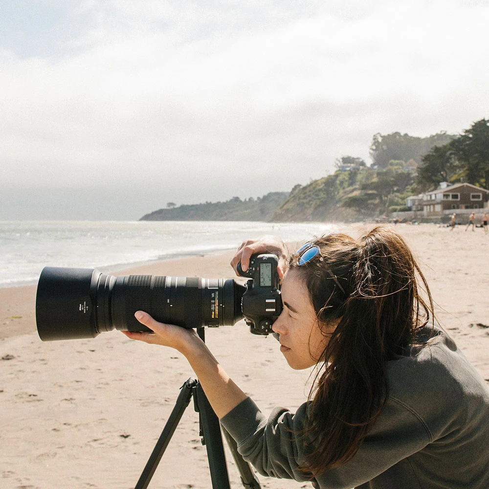 Woman photographing on the beach using a Nikon DSLR camera and telephoto lens on the Peak Design Travel Tripod