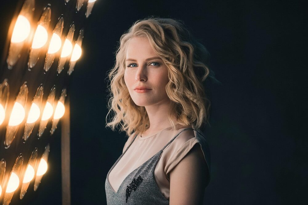 Blonde woman with blue eyes lit by studio lights
