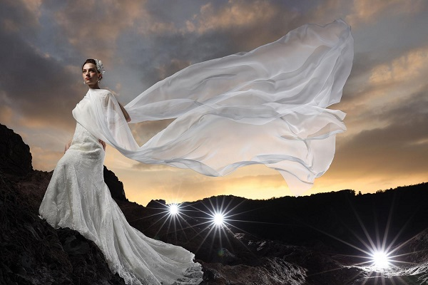 Bride in white lace gown, veil blowing in the wind, standing on rocks below a cloudy sunset, shot using Canon RF 28-70mm f2L