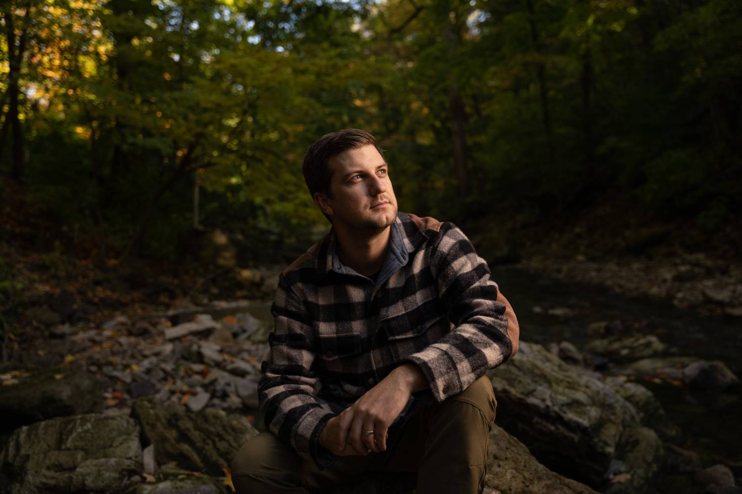 Portrait of man sitting beside river in forest, shot using Sigma 24-70mm f/2.8 DG DN Art Lens