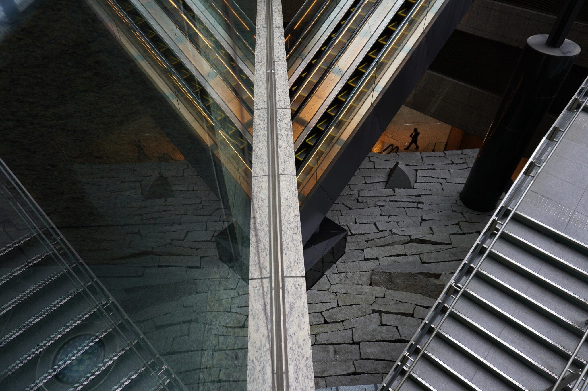 Steps, escalators and jagged stone cobbles angle towards their reflections in a glass wall, photographed with the Sony 16-50mm f/3.5-5.6 Zoom E Mount Lens