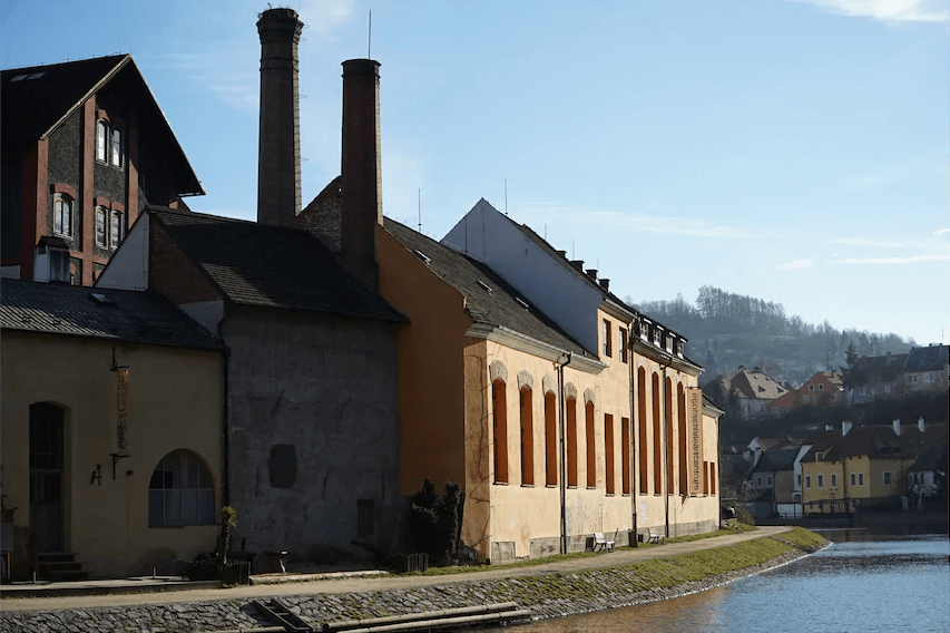 Historic yellow building on the bank of a river, photographed with the Sony E PZ 18-105mm f/4 G OSS lens