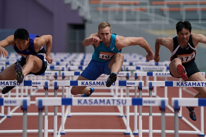 Front view of three male hurdlers jumping over hurdles, photographed with the Sony 200-600mm f5.6-6.3 G OSS lens