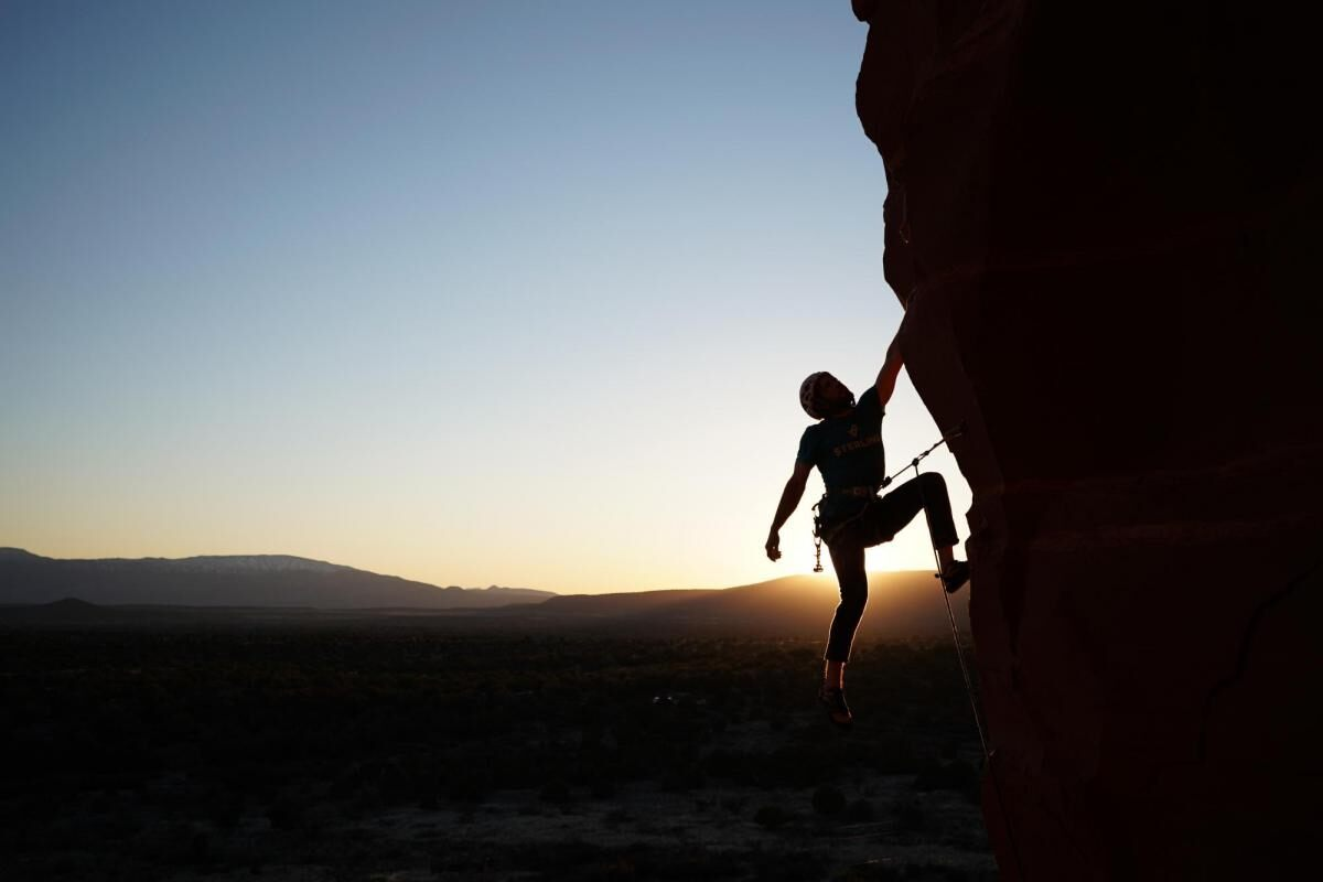Rock climber scaling a cliff, silhouetted by the sun on the horizon – photographed with the Sony 16-35mm f2.8 GM Lens