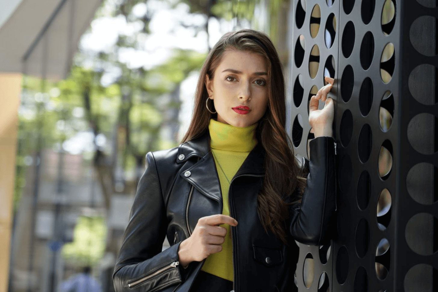 Young long-haired woman in leather jacket posing against a modern building, photographed using Sony 24-105mm f/4 G OSS Lens