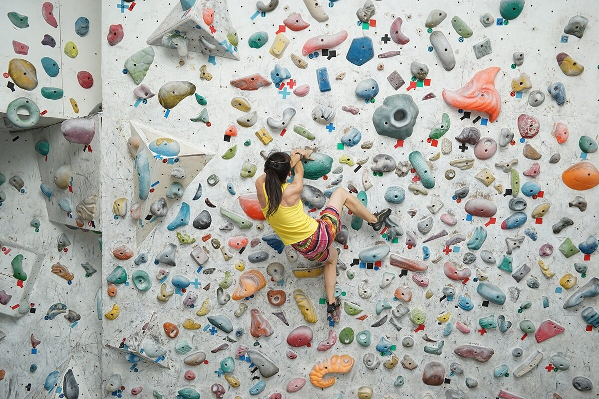 Woman indoor rock climbing up a wall of colourful grips, photographed with the Sony FE 28-70mm f/3.5-5.6 OSS lens