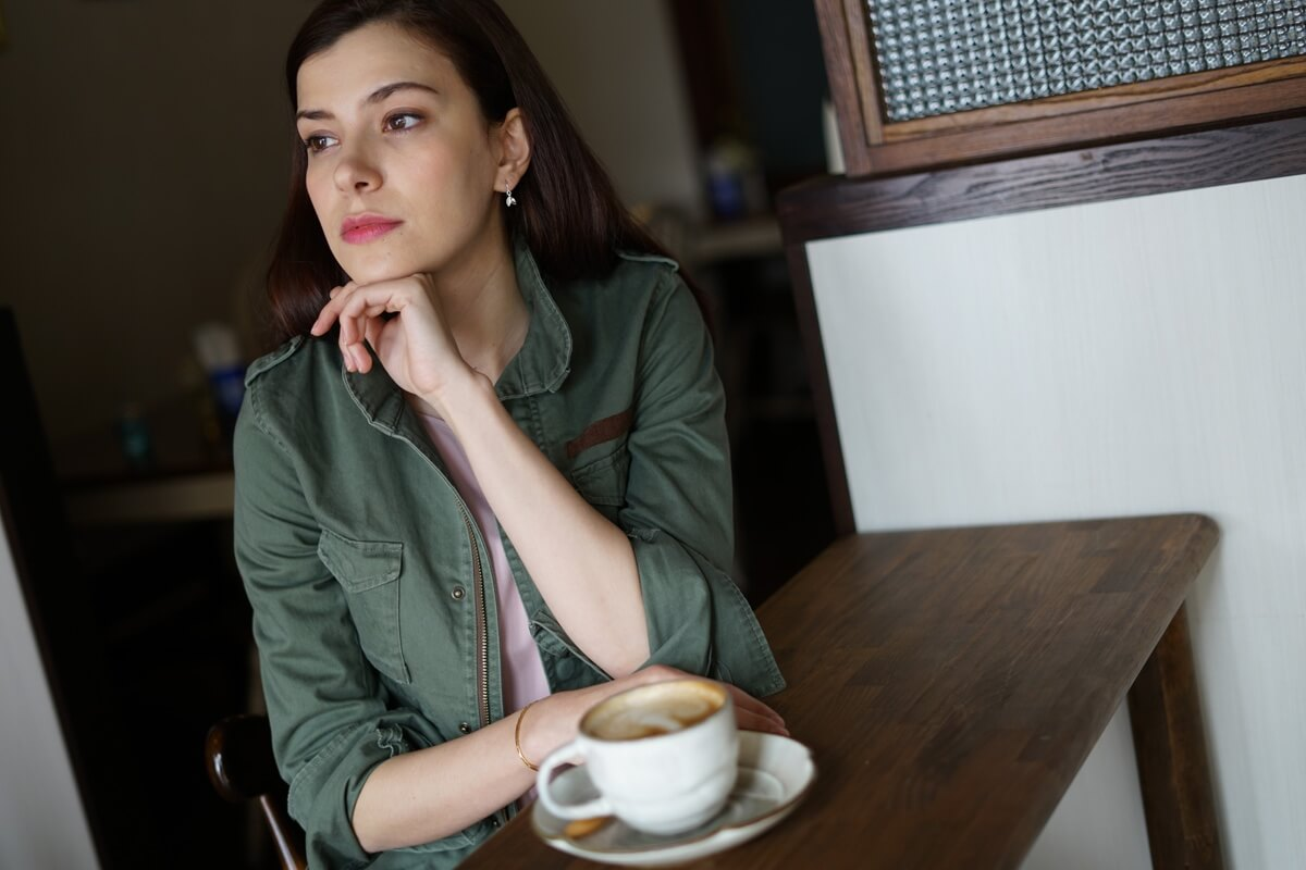 Young woman with dark hair sitting at a wooden table, beside a cup of coffee – photographed with the Sony 50mm f1.8 lens