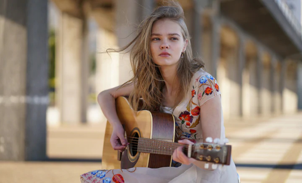 Young blonde-haired woman playing acoustic guitar with concrete bridge in the background, shot with the Sony 85mm 1.8 lens