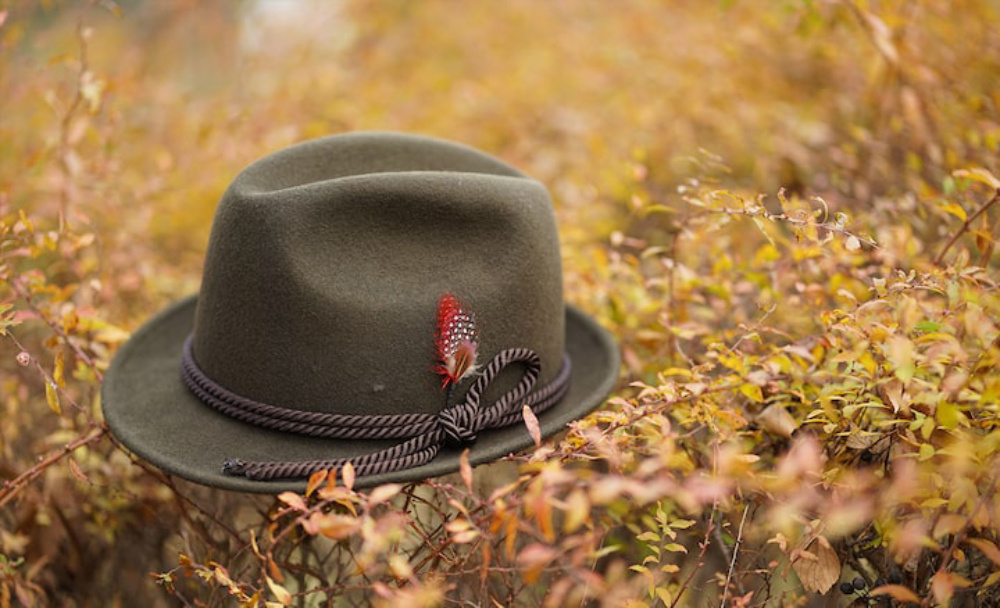 Brown trilby hat with feathers resting on an autumn coloured hedge, shot in shallow focus with the Sony 85mm 1.8 lens