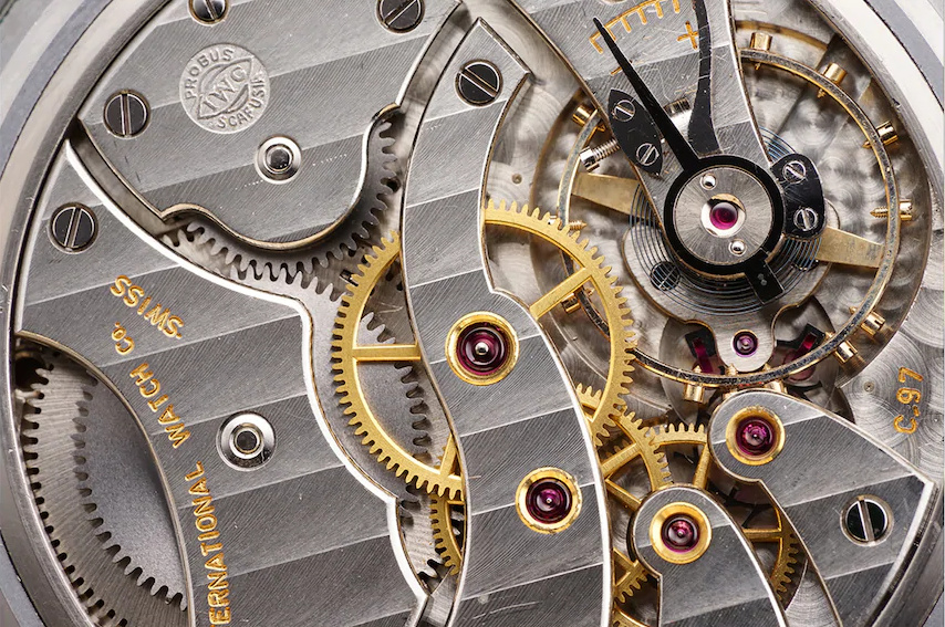 Close-up of the silver and gold interior parts of a Swiss watch, photographed with the Sony 90mm macro lens