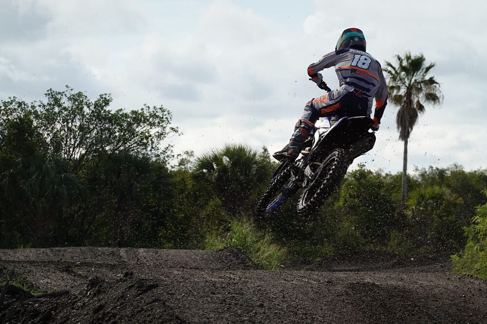 Dirt bike rider mid-air over a jump, photographed from behind with the Sony RX100 VII