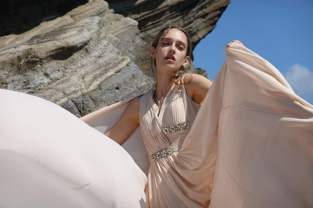 Female fashion model wearing a billowing beige dress in front of large rocks, photographed from with the Sony RX100 VII