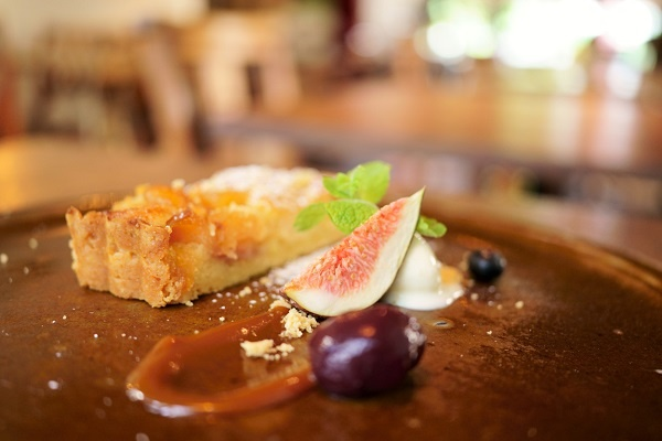 Close-up of frangipane tart slice garnished with fig, caramel and cream, photographed with the Tamron 35mm f2.8 Sony lens