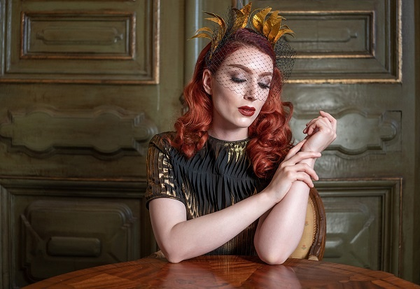 Red-haired woman wearing gold headpiece gazing at the table on which her elbows rest, shot with the Tamron 35mm f2.8 Sony lens