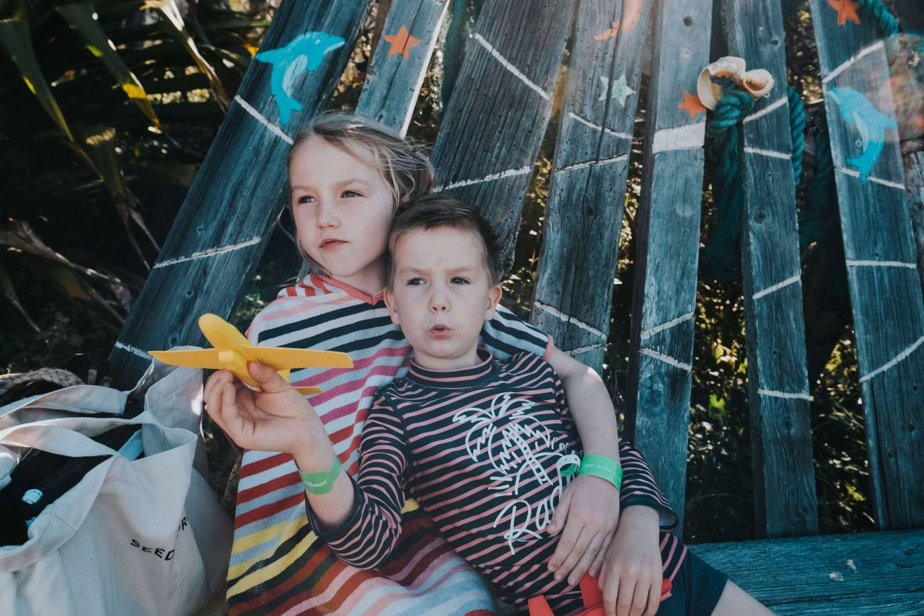 siblings sitting on a chair while playing on a yellow airplane