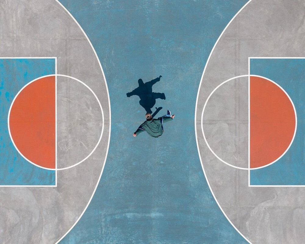 aerial photograph of a skater in a basketball court