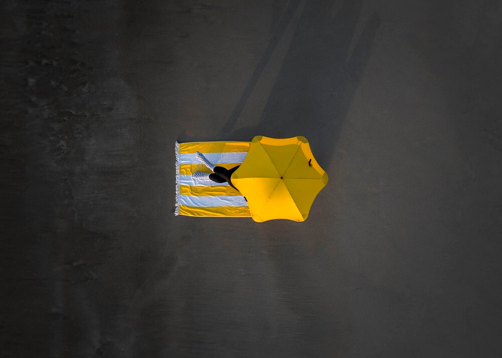 aerial photograph of a person under yellow umbrella
