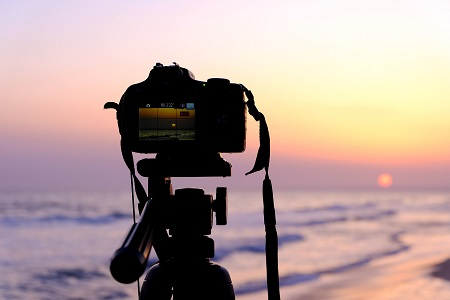 dslr camera taking a picture of the sunset