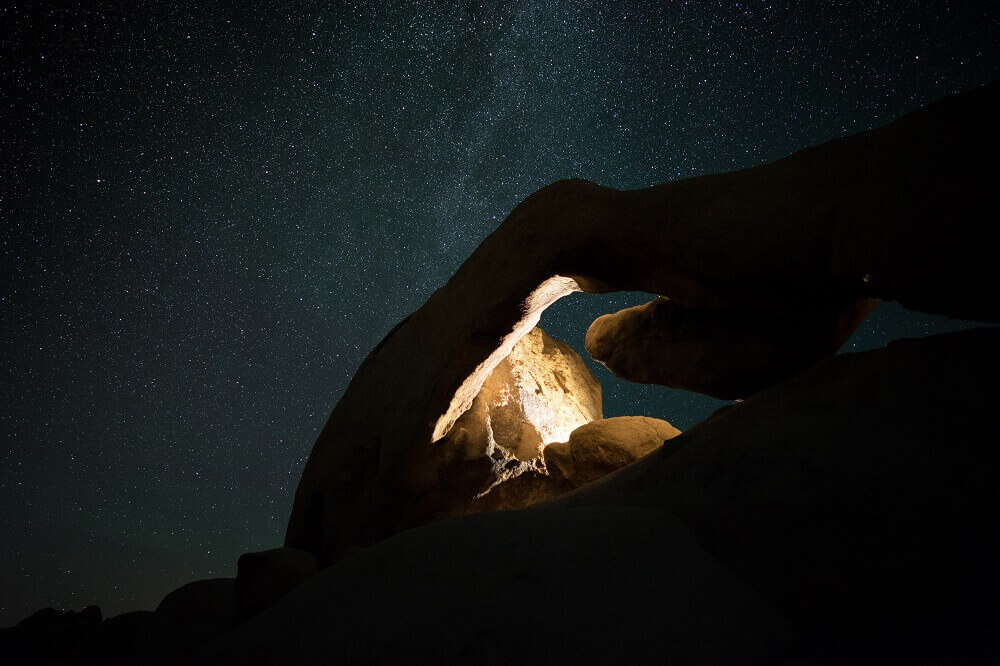 Lit up rock with stars in the background
