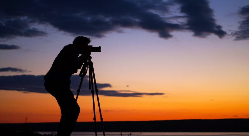 silhouette of a man with a camera and tripod shooting during sunset