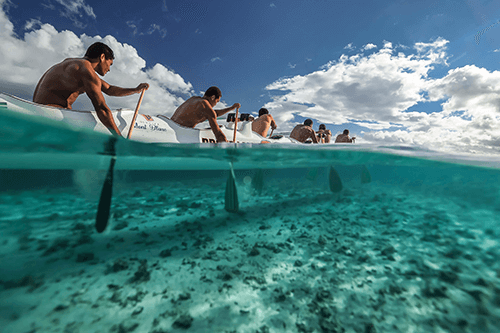 Men kayaking through shallow water, photographed half underwater on the Canon 1DX III