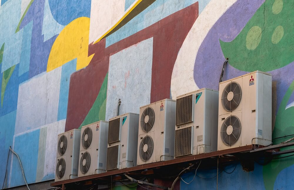 A row of condenser units in the wall of a colourful building