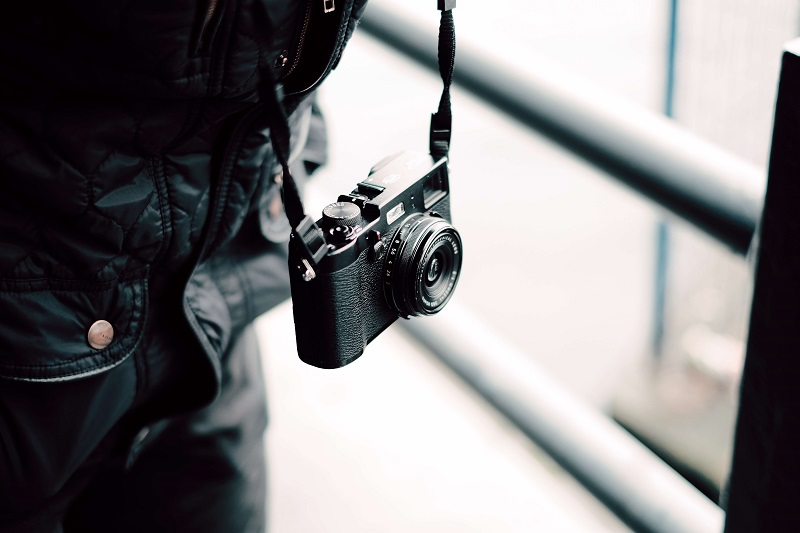 compact camera hanging on a street photographers neck
