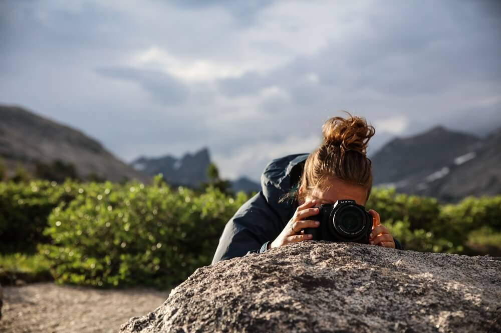 Photographer setting her camera on a rock, preparing to take a picture