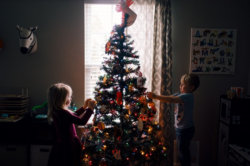 two chidlren hanging ornaments on the christmas tree