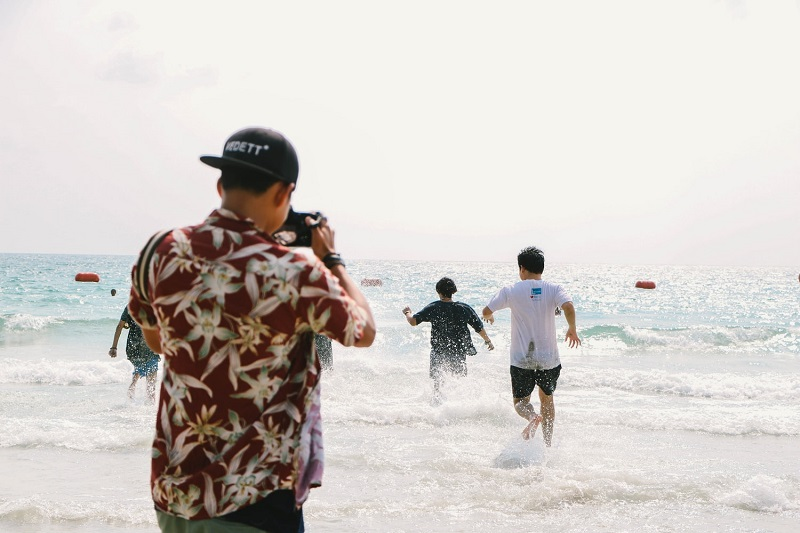 photographer taking pictures on guys running to the beach