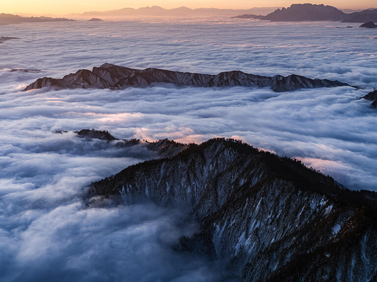 Wave-like clouds surrounding mountains under an orange-tinged sky, photographed with the Fujifilm GFX100s