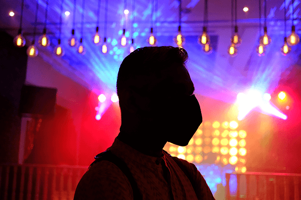 Man in a face mask silhouetted against colourful out-of-focus lights, photographed with the Fuji 27mm f2.8 R WR lens
