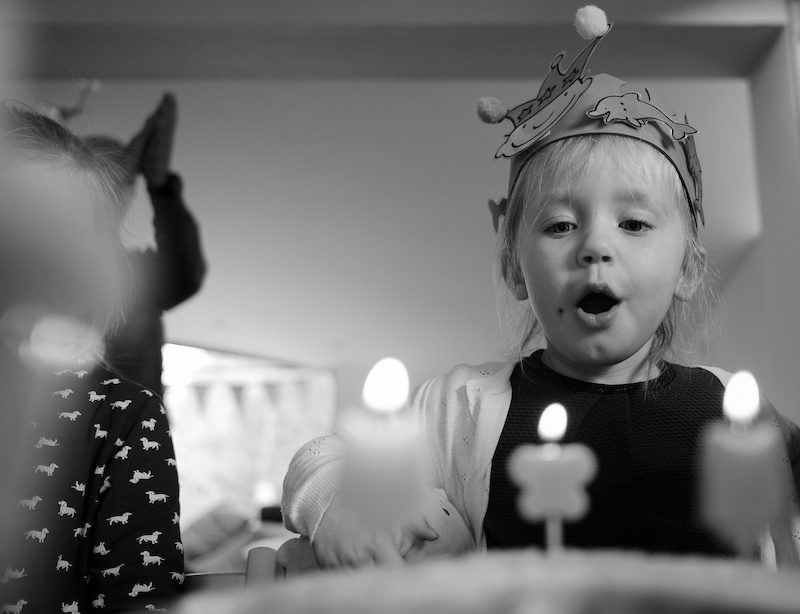 Young boy blowing candles on his birthday