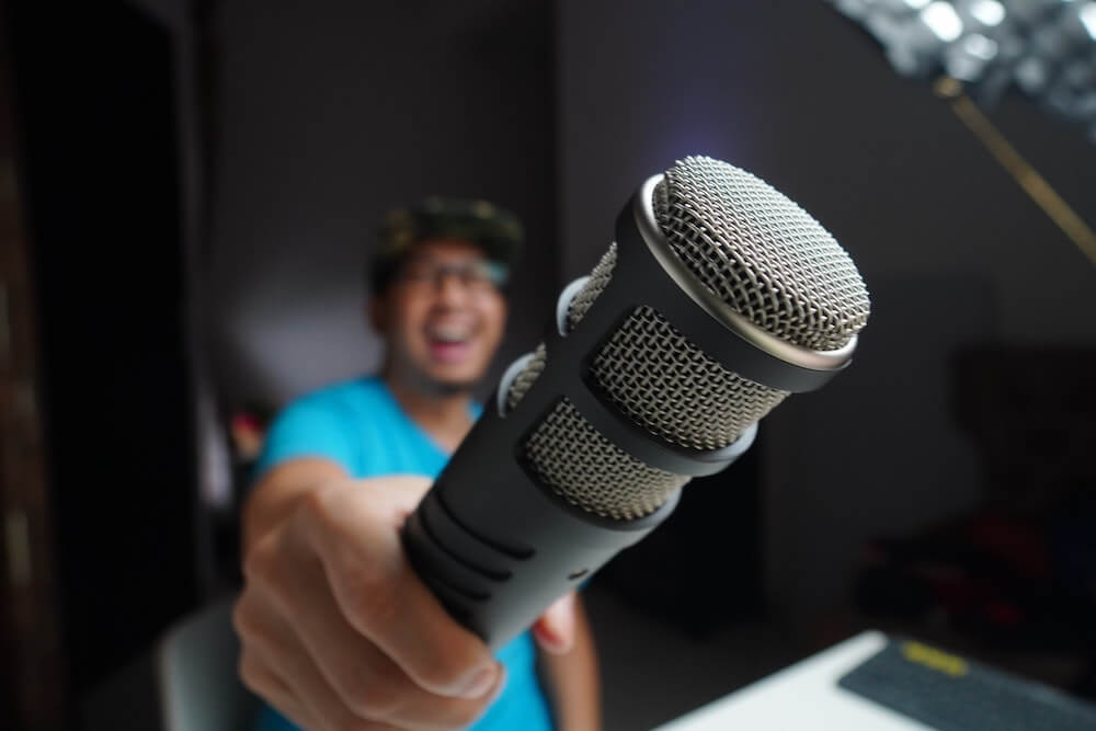 A guy in blue holding a vlogging/podcast microphone